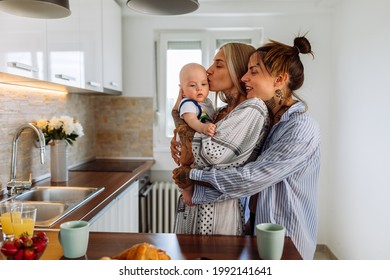 Same sex couple in pajamas hold their baby son and enjoying time spent together at home