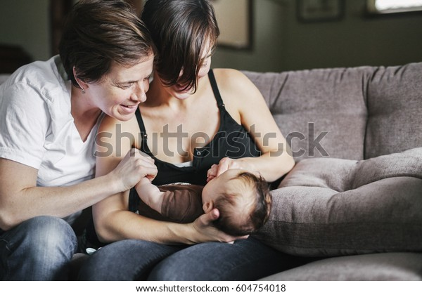 A same sex couple, two women playing with their 6 month old baby girl
