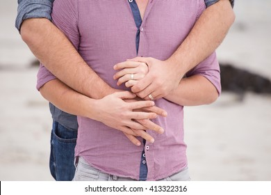 Same sex gay male couple on the beach in Cape Town South Africa looking very in love and happy.