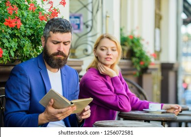 Same taste in literature. Flirt and date. Girl interested what he read. Meeting people with similar interests. Man and woman sit terrace. Literature common interest. Find person with common interest.