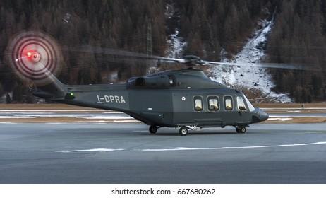SAMEDAN - December 22, 2017: Agusta Westland AW139 Prada helicopter Reg. I-DPRA land at Samedan Engadin Airport, near St. Moritz over Switzerland Alps. Military grey color helicopter during Sunset