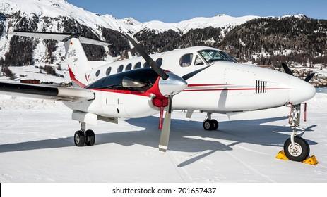 SAMEDAN ENGADIN AIRPORT - FEBRUARY 19, 2017: Beechcraft Super King Air B200 D-IICE parked over snow at St. Moritz Airport, Switzerland. Twin turbo propeller Airplane. FIS ski world championship 2017.