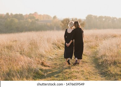 Samesex caucasian lesbian couple outdoors on the background of beautiful nature. Young stylish women hugging at sunset, affectionate and happy.