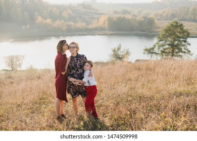 Samesex caucasian lesbian family with a child and a dog walking outdoors on the background of beautiful nature. Mothers having fun with their son.