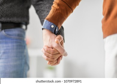 same-sex relationships, lgbt and homosexual concept - close up of male gay couple holding hands