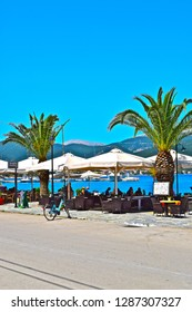 Sami, Kefalonia / Greece - 5/21/2018: A harbourside restaurant in the port of Sami. With palm trees and sunshades for diners. Hot sunny day blue sky and sea. Mountains in background.