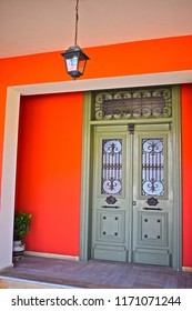 Sami, Kefalonia / Greece - 5/21/2018: Traditional ornate front door to apartment in Sami on the Greek holiday island of Kefalonia / Cephalonia. The orange walls contrast with door & hanging lamp over.