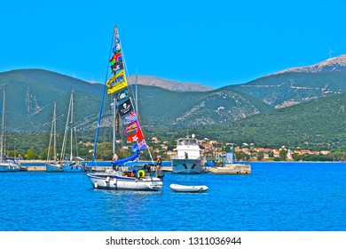 Sami, Kefalonia / Greece - 5/21/2018: A yacht with a colourful display of flags sails into the idyllic setting of Sami harbour with a stunning backdrop of tree-covered mountains. Deep blue sky and sea