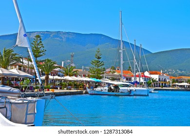 Sami, Kefalonia / Greece - 5/21/2018:Blue sky and sea at the pretty port of Sami, with yachts moored in harbour & people relaxing in restaurants overlooking the sea. Beautiful mountains in background.