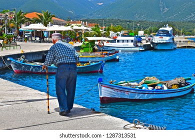 Sami, Kefalonia / Greece - 5/21/2018:Old Greek man with walking step walks along the harbour at the beautiful port of Sami.Traditional fishing boats moored behind. Colourful island scene.