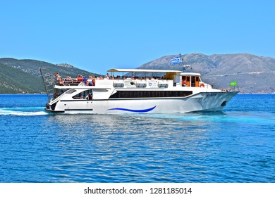 Sami, Kephalonia / Greece - 5/21/2018: The popular sea trip to the nearby island of Ithiki or Ithaca  departs from Sami harbour on the holiday island of Cephalonia or Kefalonia with mountains behind.
