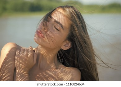 Sammer day. Woman with long brunette hair, hairstyle, on sunny summer day. Woman with healthy face skin, naked shoulders, beauty.