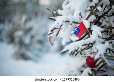 Samoa flag. Christmas background outdoor. Christmas tree covered with snow and decorations and Samoan flag. New Year / Christmas holiday greeting card.