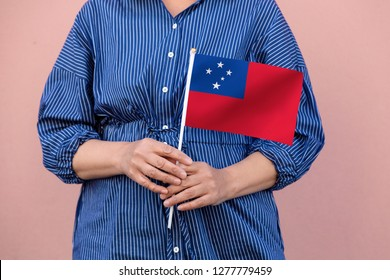 Samoa flag. Close up picture of woman's hands holding a national flag of Samoa.