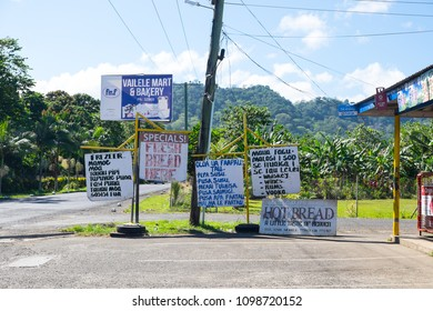 Samoa, South Pacific - October 27, 2017: Samoan and English signs outside a shop and bakery on Upolu Island, with green foliage in background