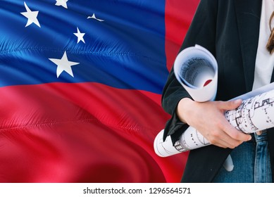 Samoan Architect woman holding blueprint against Samoa waving flag background. Construction and architecture concept.