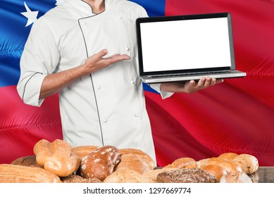 Samoan Baker holding laptop on Samoa flag and breads background. Chef wearing uniform pointing blank screen for copy space.