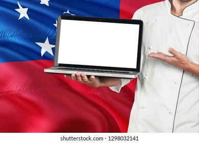 Samoan Chef holding laptop with blank screen on Samoa flag background. Cook wearing uniform and pointing laptop for copy space.