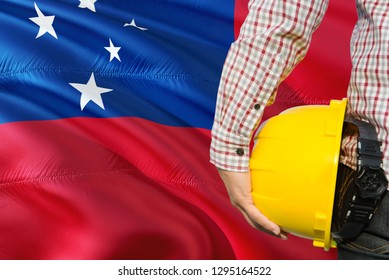 Samoan Engineer is holding yellow safety helmet with waving Samoa flag background. Construction and building concept.