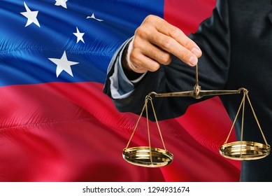 Samoan Judge is holding golden scales of justice with Samoa waving flag background. Equality theme and legal concept.