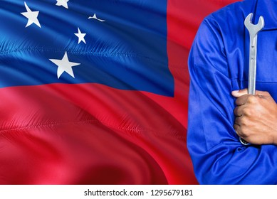 Samoan Mechanic in blue uniform is holding wrench against waving Samoa flag background. Crossed arms technician.