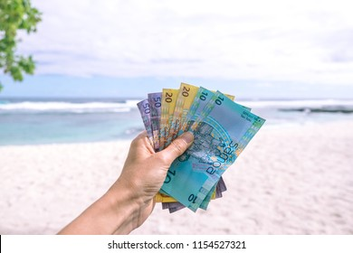 Samoan Tala currency (WST) - left hand holding colorful bank notes from Western Samoa against backdrop of South Pacific ocean and beach