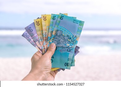 Samoan Tala currency (WST) - left hand holding colorful bank notes from Western Samoa in South Pacific