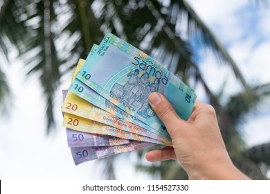Samoan Tala currency (WST) - right hand holding colorful bank notes from Western Samoa in South Pacific with palm trees in background