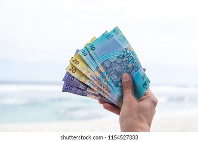Samoan Tala currency (WST) - right hand holding colorful bank notes from Western Samoa in South Pacific