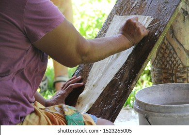 A Samoan woman cleans the inner bark with a shell scraper, using a sloping board for support when making the bark cloth, Siapo.