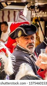 Samobor, Croatia, October 20, 2018. Traditional soldier closeup portrait wearing traditional uniform and hat with glass of vine and looking behind