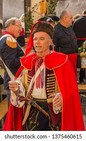Samobor, Croatia, October 20, 2018. Traditional soldier closeup portrait wearing traditional uniform and hat with glass of vine and singing
