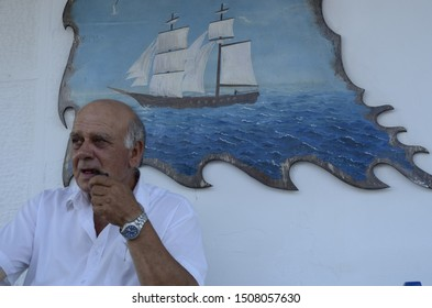 Samos island, Greece -July 23, 2015: Old man front of traditional Greek tavern in Samos island, Greece.