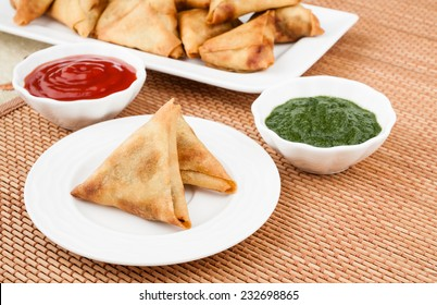 Samosa with Mint Chutney - Closeup view of delicious deep fried south Indian samosa with mint chutney and tomato sauce.