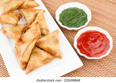 Samosa with Mint Chutney - Overhead view of delicious deep fried south Indian samosa with mint chutney and tomato sauce.