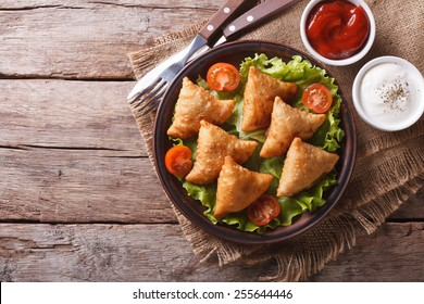 samosa on a plate with sauce and tomatoes. horizontal view from above, rustic style