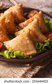 samosa on a plate with tomatoes and lettuce on a wooden table. Vertical close-up