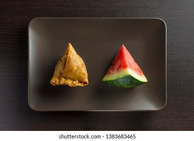 A samosa and a slice of watermelon in a dish on dark background. Top view. Conceptual photo for healthy eating. Image 1 of 3.