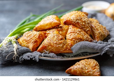 Samosas with meat on a plate with linen cloth on a dark textured background, selective focus.