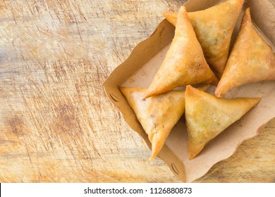 Samosas on brown papaer tray on rustic wood.Top view.