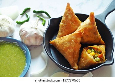 Samosas with vegetables filling served in cast iron skillet on marble table background with green chili, onion and mint cilantro dipping sauce. Home cooking popular deep fried snack. (space for text)