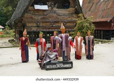 SAMOSIR ISLAND, NORTH SUMATRA INDONESIA - 22 JUNE 2016: Artisits wearingtraditional batak-style clothes at open air Huta Bolon Simanindo Batak Museum