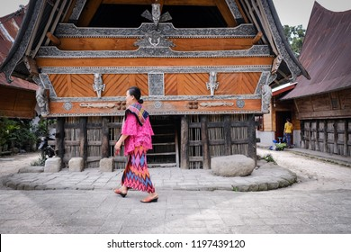 Samosir, North Sumatera/Indonesia-Auguts 2018: A Batak woman with traditional Batak dress passes the old house in Huta Siallagan village in Samosir. Some local people still use this   house to live.
