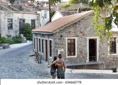 SAMOTHRACE GREECE - AUGUST 12 2016: Greece, Samothrace, A couple walking at the mountain village Chora on the island in aegean sea. The sign says ''Art, Fashion''