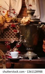 Samovar with a cup of tea. Cup of tea and a Russian samovar under the light of a lantern. Autumn.