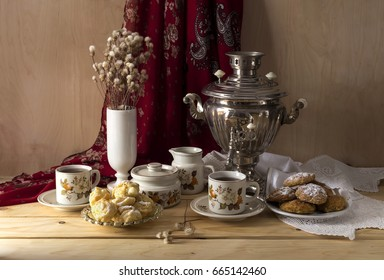 Samovar, cups of tea, biscuits and cakes on the table closeup