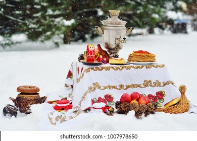 Samovar, pancakes with red caviar, bagels, nested dolls, Khokhloma-style dishes on a table in the background of the forest and snow. Russia, the carnival celebration. Maslenitsa, Shrovetide.