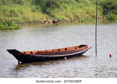 Sampan boat parked in the middle of the river. It is a small boat of a kind used in East Asia, typically with an oar or oars at the stern.