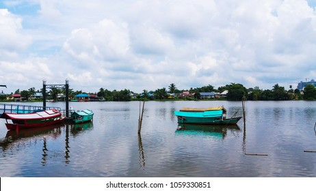 Sampan boat in vivid color view with reflection rest in the middle of the river at Kuching , Sarawak river.
