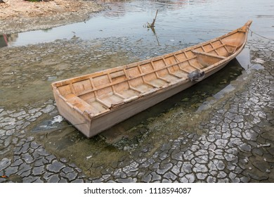 """A Sampan Boat""""wooden boat"""" in Dry lake land surface with natural texture of cracked clay in perspective floor"""